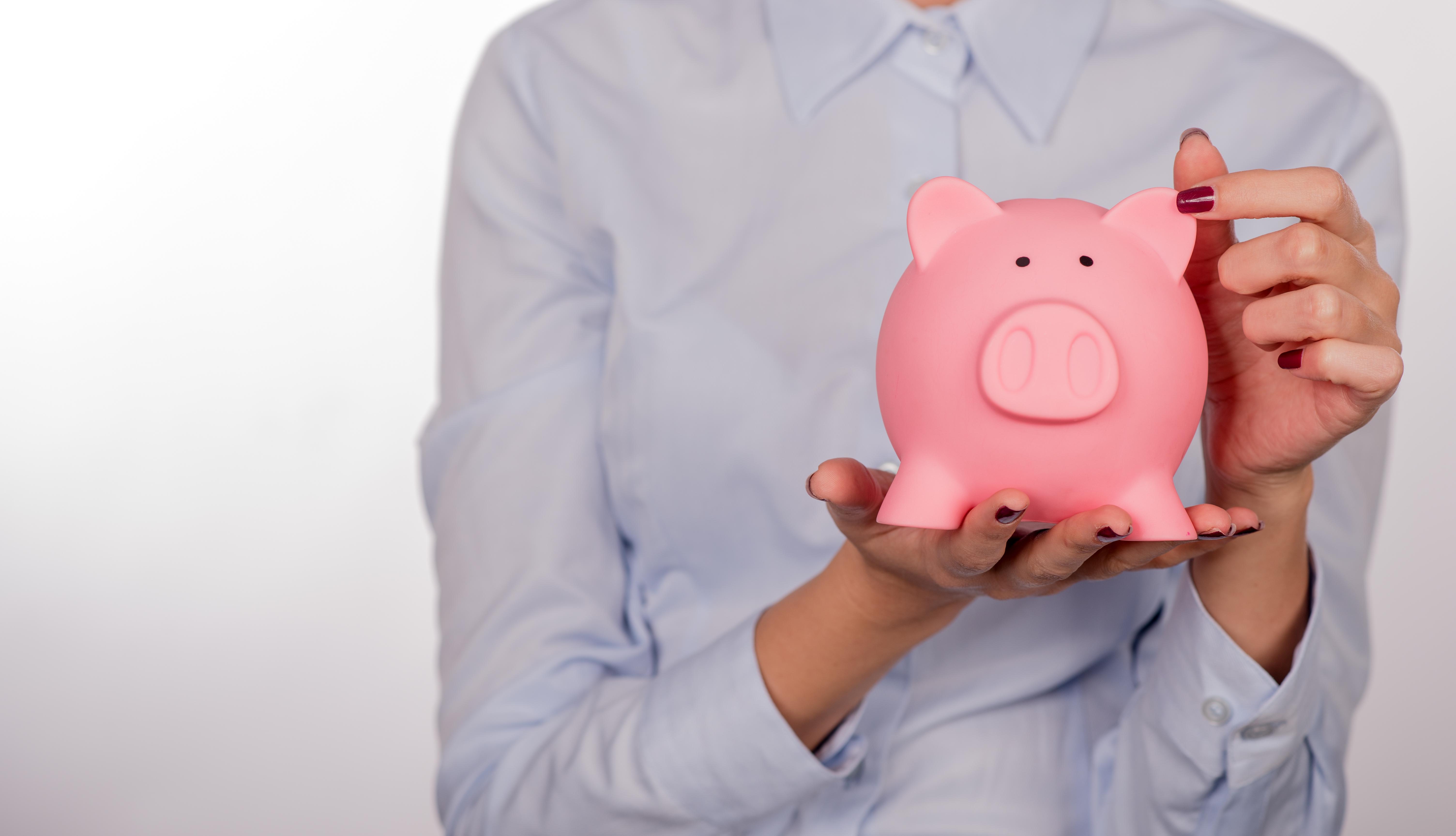 Piggy bank savings woman smiling happy. Female holding piggy ban